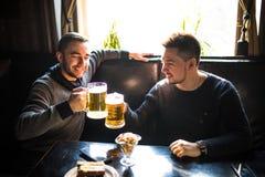 Sammanträde för ung man två i baren som äter och dricker öl på baren royaltyfri foto