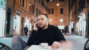 Sammanträde för ung man utanför i stadskafét i aftonen Stiligt manligt samtal med vännen, använder smartphonen stock video