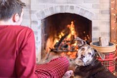 Sammanträde för ung man vid brand med hunden arkivbild