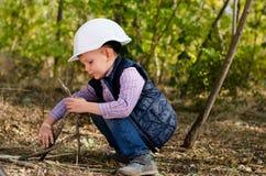 Sammanträde Little Boy med hjälmen som spelar pinnar arkivfoto