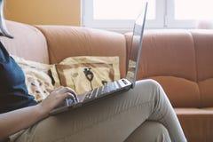 Sammanträde och arbete för ung kvinna på bärbara datorn som är inomhus med solljus Royaltyfri Bild
