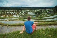 Sammanträde och att koppla av för handelsresande för ung man som var utomhus- på risfält terrasserade på, i Bali Indonesien Fotografering för Bildbyråer
