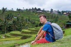 Sammanträde och att koppla av för handelsresande för ung man som var utomhus- på risfält terrasserade på, i Bali Indonesien Arkivfoton
