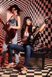 Sammanträde och stås kvinnor leker den elektriska gitarren och allsång Arkivfoton