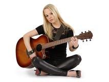 Sammanträde på den leka gitarren för däcka Royaltyfri Foto
