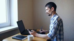 Sammanträdebärbar dator för ung man och setelefon stock video