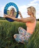 Sammanträdeflicka med en spegel Royaltyfri Fotografi