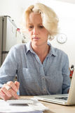 Sammanträdekvinnan koncentrerar, medan beräkna Financials på Compu Arkivbilder