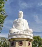 Sammanträdestaty av en vit Buddha, mot en blå himmel, grön vegetation Arkivbilder