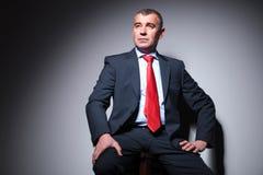 Sammanträde för affärsman på en stol, mot grå bakgrund Royaltyfri Foto