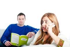 Sammanträde för den unga kvinnan på den hemmastadda soffan och att tala på en mobil stund hennes pojkvän läser Arkivfoto