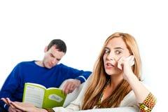 Sammanträde för den unga kvinnan på den hemmastadda soffan och att tala på en mobil stund hennes pojkvän läser Arkivbilder