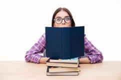 Sammanträde för ung kvinna på tabellen med böcker Arkivbild