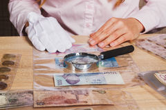 Sammelbare Münzen und Banknoten in den Zellen und in der Lupe Stockfotos