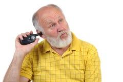 Sammeln des älteren kahlen Mannes sein Ohr Lizenzfreie Stockfotografie
