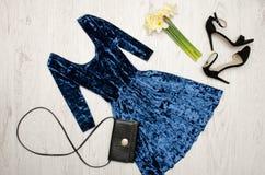 Sammetblått klär, svärtar skor, kopplingen och en bukett av påskliljor trendigt begrepp spelrum med lampa Royaltyfria Bilder