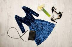 Sammetblått klär, svärtar skor, kopplingen och en bukett av påskliljor trendigt begrepp spelrum med lampa Arkivbilder