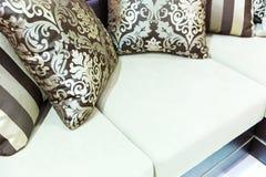 Sammetkuddar på den bruna soffan Arkivbilder