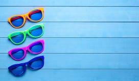 Sammlung bunte Sonnenbrille auf blauem hölzernem Hintergrund Stockbild