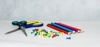 Sammlung verschiedene Druckbolzen auf weißem Hintergrund, Scheren und Bleistiften Lizenzfreies Stockfoto
