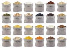 Sammlung verschiedene Getreide, Körner und Flocken in den Taschen lokalisiert auf weißem Hintergrund lizenzfreie stockfotos