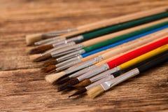 Sammlung verschiedene Malerpinsel auf hölzernem Brett Stockfotografie
