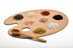 Sammlung verschiedene Salze auf der hölzernen Palette lokalisiert auf Weiß Stockfotografie