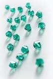 Sammlung vieler grünen doppelten Kegel-Kristalle in einem weißen Kasten Lizenzfreies Stockfoto