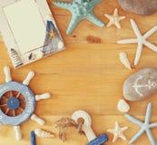 Sammlung von See und setzen die Gegenstände auf den Strand, die einen Rahmen über hölzernem Hintergrund schaffen, Stockbilder