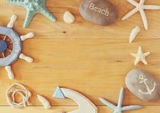 Sammlung von See und setzen die Gegenstände auf den Strand, die einen Rahmen über hölzernem Hintergrund schaffen, Stockfoto