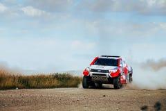 Sammlungs-Toyota-Autofahrten auf staubige Straße Lizenzfreies Stockfoto