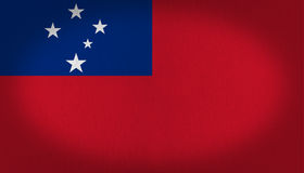 Samoa flag. With a dark blue rectangle at the top left side with five white stars on it, over a red back, fabric texture background Stock Image