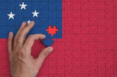 Samoa flag is depicted on a puzzle, which the man`s hand completes to fold.  stock illustration