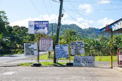 Samoa, South Pacific - October 27, 2017: Samoan and English sign. S outside a shop and bakery on Upolu Island, with green foliage in background royalty free stock photo