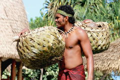 A Samoan man carrying coconuts in a traditionally woven pair of baskets. Honolulu, Hawaii - May 27, 2016:A Samoan man carrying coconuts in a traditionally woven stock images