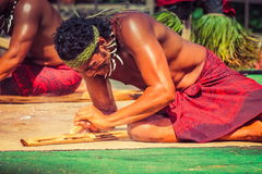 A Samoan man demonstrates how to start fire by rubbing sticks. Honolulu, Hawaii - May 27, 2016:A Samoan man demonstrates how to start fire by rubbing sticks in royalty free stock photography