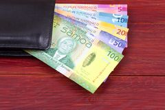 Samoan money in the black wallet. On a wooden background royalty free stock image