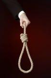 Samobójstwa i biznesu temat: Ręka biznesmen trzyma pętlę arkana dla wieszać na zmroku w czarnej kurtce - czerwień odizolowywająca Obraz Stock