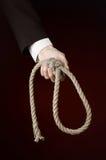 Samobójstwa i biznesu temat: Ręka biznesmen trzyma pętlę arkana dla wieszać na zmroku w czarnej kurtce - czerwień odizolowywająca Zdjęcia Stock