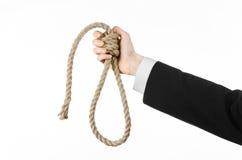 Samobójstwa i biznesu temat: Ręka biznesmen trzyma pętlę odizolowywająca arkana dla wieszać na bielu w czarnej kurtce Zdjęcia Stock