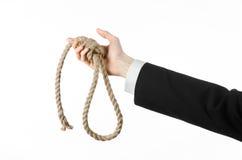 Samobójstwa i biznesu temat: Ręka biznesmen trzyma pętlę odizolowywająca arkana dla wieszać na bielu w czarnej kurtce Obrazy Royalty Free