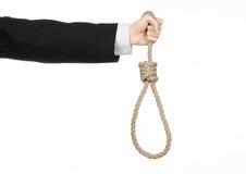 Samobójstwa i biznesu temat: Ręka biznesmen trzyma pętlę odizolowywająca arkana dla wieszać na bielu w czarnej kurtce Zdjęcia Royalty Free