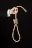Samobójstwa i biznesu temat: Ręka biznesmen trzyma pętlę odizolowywająca arkana dla wieszać na czerni w czarnej kurtce Zdjęcie Stock