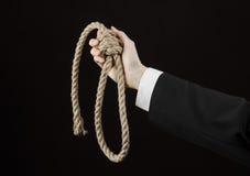 Samobójstwa i biznesu temat: Ręka biznesmen trzyma pętlę odizolowywająca arkana dla wieszać na czerni w czarnej kurtce Fotografia Stock