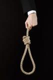 Samobójstwa i biznesu temat: Ręka biznesmen trzyma pętlę odizolowywająca arkana dla wieszać na czerni w czarnej kurtce Obrazy Royalty Free