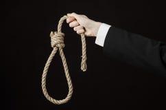 Samobójstwa i biznesu temat: Ręka biznesmen trzyma pętlę odizolowywająca arkana dla wieszać na czerni w czarnej kurtce Zdjęcie Royalty Free