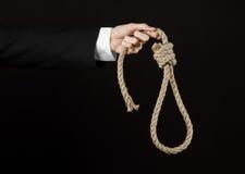 Samobójstwa i biznesu temat: Ręka biznesmen trzyma pętlę odizolowywająca arkana dla wieszać na czerni w czarnej kurtce Obraz Stock