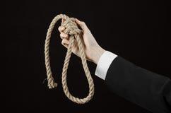 Samobójstwa i biznesu temat: Ręka biznesmen trzyma pętlę odizolowywająca arkana dla wieszać na czerni w czarnej kurtce Zdjęcia Stock