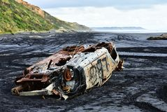 Samochód łapiący przypływem i opuszczać na czarnym piasku Karioitahi plaża zaniechany, Nowa Zelandia zdjęcia royalty free