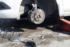 Samochód bez koła i podnosi up hydraulicznym, czekający opony zastępstwo obraz stock